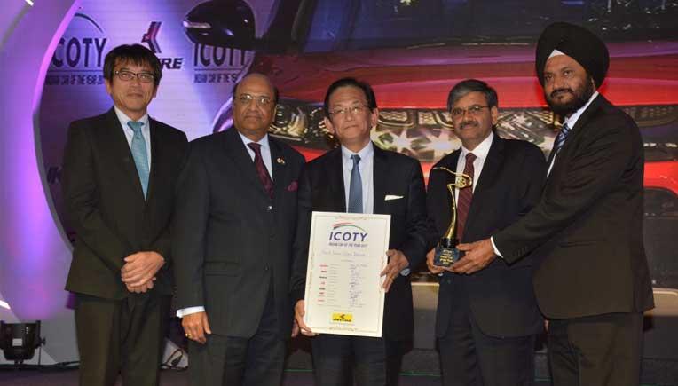 Dr. Raghupati Singhania of JK Tyre & Industries Limited, presenting the Indian Car of the Year Award 2017 to Kenichi Ayukawa and Randhir Singh Kalsi of Maruti Suzuki