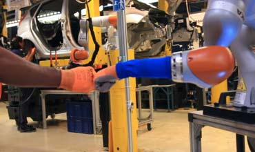 Car workers buddy up with robots in Ford factory